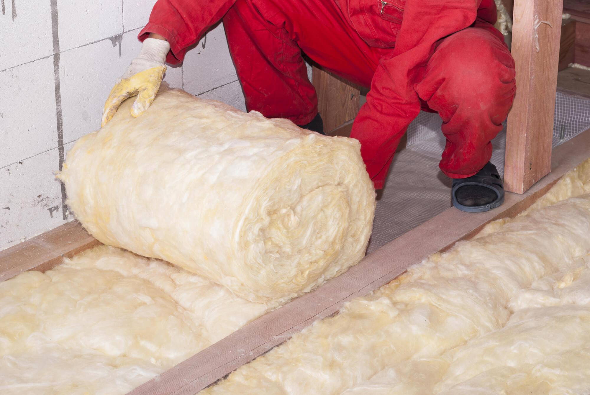isolation du plancher par un professionnel avec gants qui déroule des rouleaux de laine