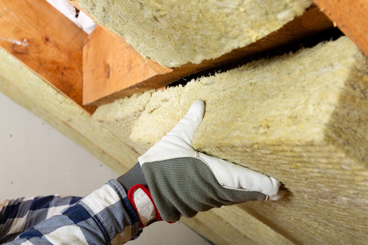 mains d'un artisan qui pose un panneau isolant en rampant de toiture