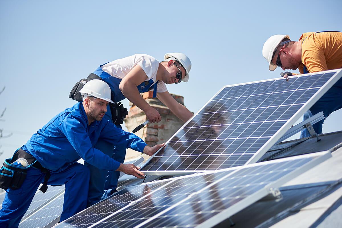trois professionnels posent un panneau solaire sur un toit